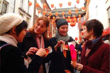 Group of people eating Chinese food on Chinese New Year in Chinatown, London, England