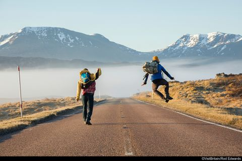 Rear view of two men jumping with joy on a country road in Glen Coe, Scottish Highlands, Scotland.