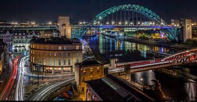 Night time view of the Tyne Bridge, Swing Bridge and Sandhill, Newcastle-upon-Tyne, England lit up at night.