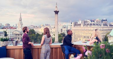 People having a drink at The Rooftop St. James, Trafalgar St. James Hotel, Trafalgar Square, London, with Nelson's Column in the background.