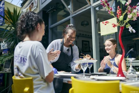 Smiling woman serving food to two women at Etta's Seafood Restaurant, Brixton Village Market, Brixton, London, looking at camera.