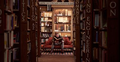 Man sitting on a sofa, reading a book at Barter Books, a secondhand bookshop in Alnwick, Northumberland.