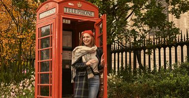 Young woman at a red phone box outside St Pauls Cathedral