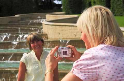 Two female tourists in Northumberland, a woman in pink taking a photo of a woman in green by a fountain