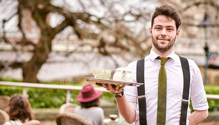 Smiling waiter wearing apron and holding a tray standing at an outdoor table of a restaurant in York, North Yorkshire, England.