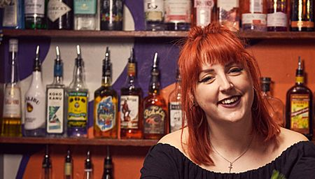 Smiling woman with red hair standing behind the bar of a pub in York, North Yorkshire, England.