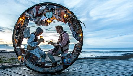 Two men sitting in a wheel during a performance at Acrojou, Wheel House performing in Staithes.