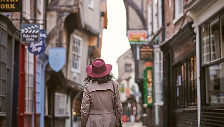 Woman wearing trench coat and pink hat walking through narrow historic street of York, North Yorkshire, England.
