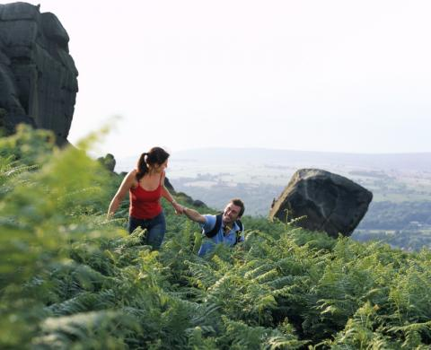 A young couple hiking in the countryside an example of an activity undertaken in Britain