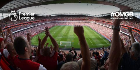 Wide angle shot of a green football pitch surrounded by seats