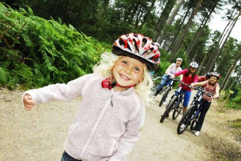Image of a young blonde girl wearing a helmet infront of a group of people on bikes