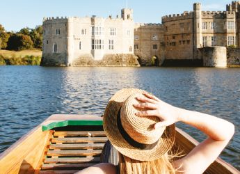 woman sitting in a rowing boat on a river next to a castle