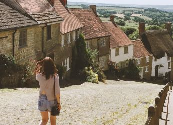 A young woman walking down Gold Hill in Shaftesbury, Dorset