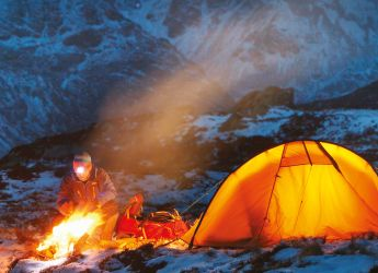 An orange tent on a blue hillside with a campfire