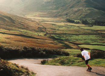 A young man skateboarding down a windy road in Cumbria