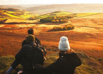 A couple watching a sunset over the countryside