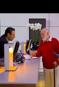 An elderly man with a walking stick talking to a hotel receptionist