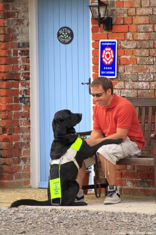 Man with assistance dog outside cottage