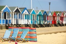 colourful beach huts and deck chairs along the beach front in Southwold