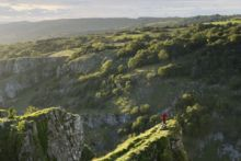 A person in a red jacket standing on a ledge looking at the view of Cheddar Gorge, a limestone gorge in the Mendip Hills