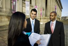 Three business people in discussion outside St George's Hall