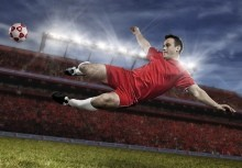 A footballer in a red football kit kicking the ball in a stadium filled with people