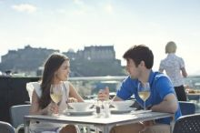 Couple having lunch outside with a castle in the background