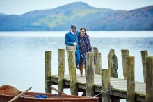 A couple walking on a small wooden dock at Coniston Water in the Lake District