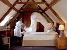 Chambermaid at Whatley Manor making the bed in preparation for guests' arrival