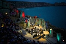A music performance taking place at Minack Theatre in Cornwall by the coast
