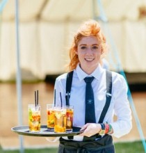 A young woman waitress in her uniform holding a tray of drinks to serve