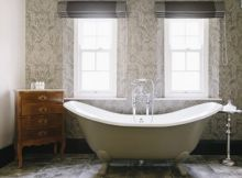 Bathtub in a bathroom with ornate wallpaper in a luxury hotel