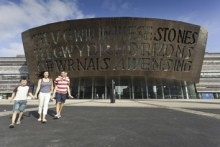 A family walking in front of the Millennium Centre in Cardiff, Wales