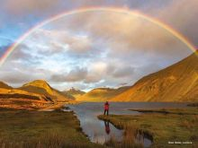 man stood looking out over rainbow over vast water in cumbria