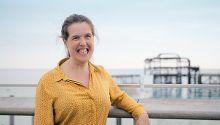 Comedian Rosie Jones smiling in Brighton with burnt pier in background
