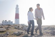 Two people, a couple holding hands, walking over the rocks, on Portland Bill headland overlooking the Portland Bill lighthouse on the Isle of Portland.