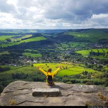 Girl in a yellow jacket sitting on the top of the hill