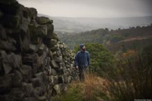 A man walking beside a dry stone wall with a rural valley view behind.