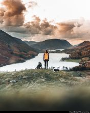 Girl and dog walking on a hill in cumbria overlooking a lake
