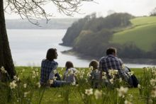 Family sitting on grass at Trelissick Garden, Cornwall, England, UK