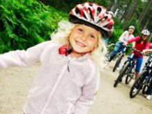 Young blonde girl in a helmet in front of a group of people on bikes