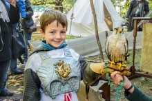 Young boy in Armour holding a bird