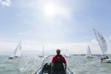 Man steering motorized dinghy following sailboats on Solent, Isle of Wight.