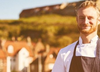 a chef looks at the camera with a village in the background