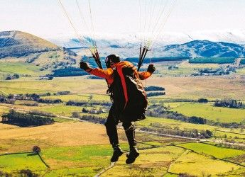 a young woman jumping in the air with the countryside in the background