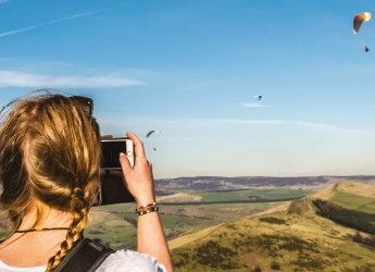 A woman taking a photo of the Derbyshire countryside