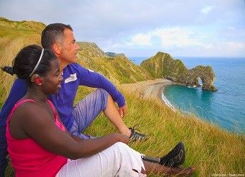 Lady with hearing loss and male amputee admiring view of Lulworth Cove