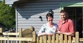 two business owners outside a log cabin looking at the camera