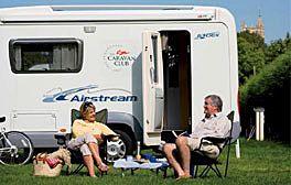 A couple outside their caravan