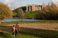 Couple walking in field with castle in distance